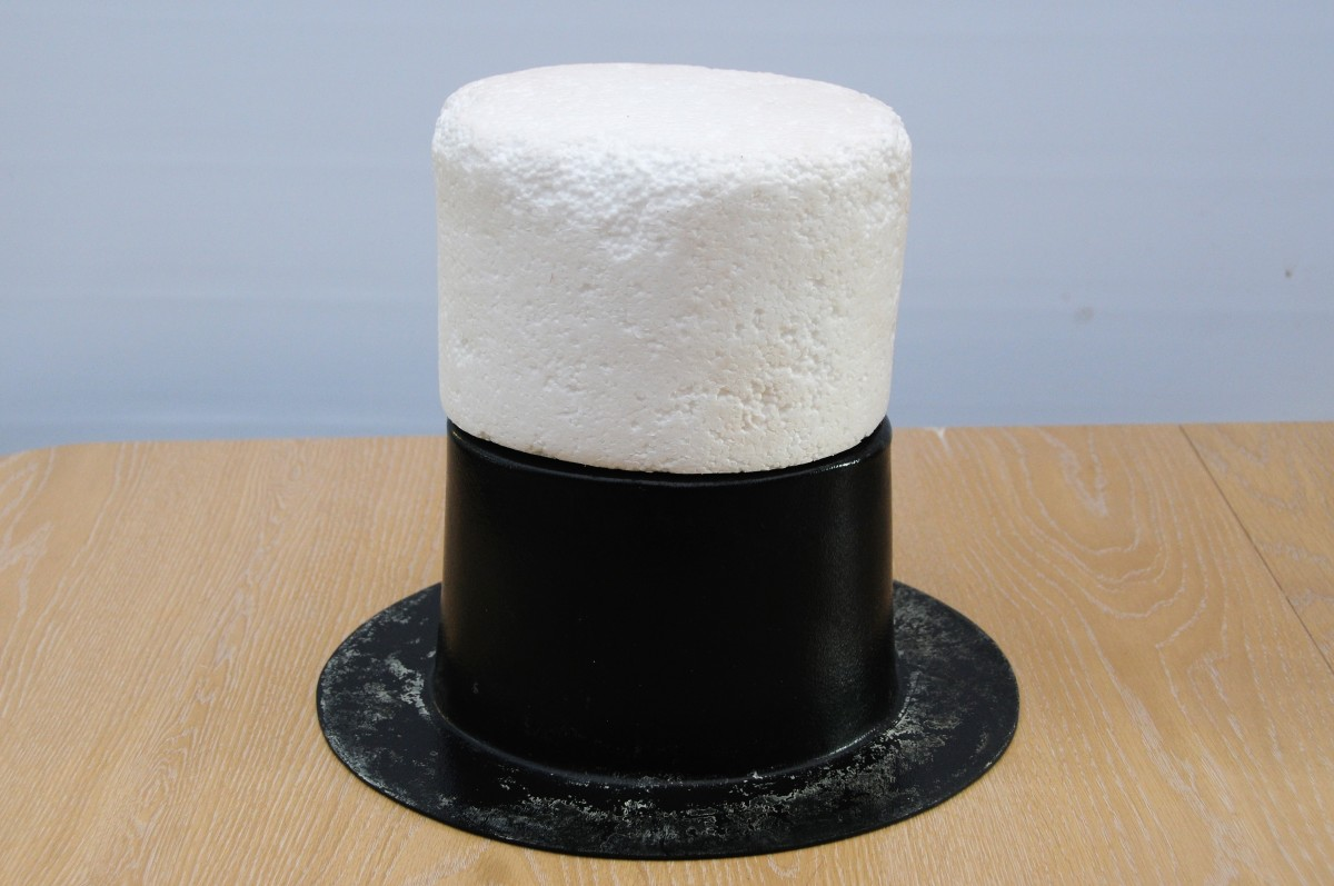 The polystyrene hat block balanced on the hat shaper.  This was used inside the waste-paper bin sleeve to increase the height of the hat.