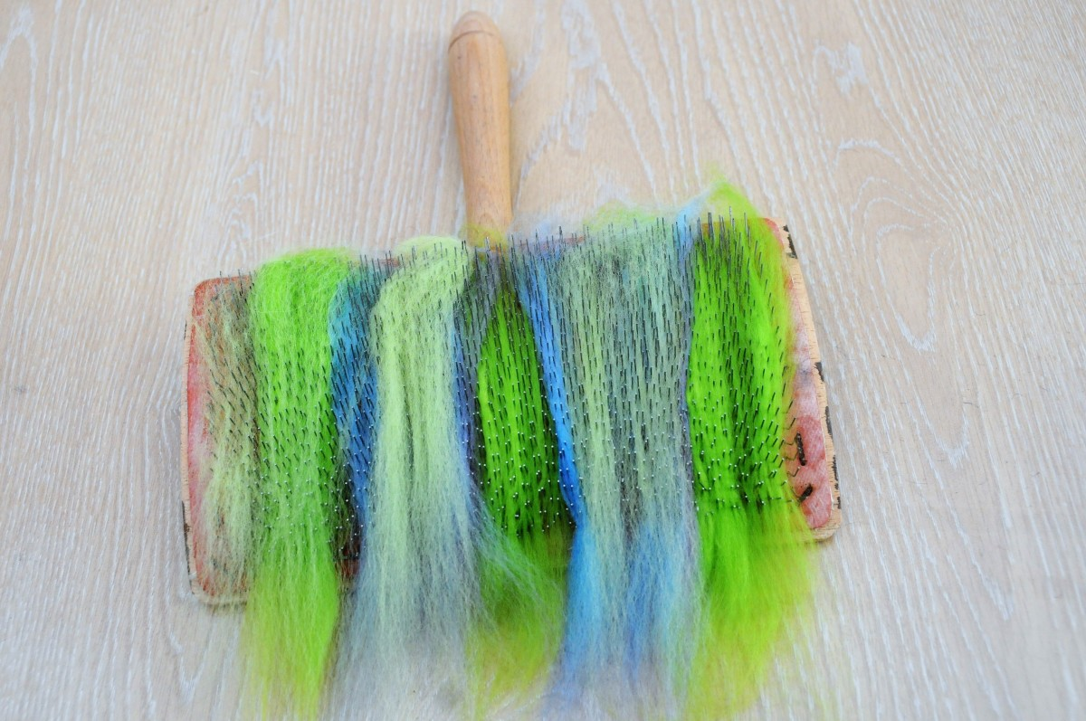 Add different colours of wool roving to the teeth on the hand carders