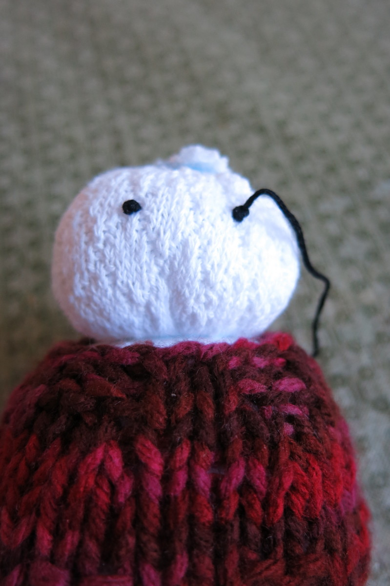 Sewing eyes on your sock snowman