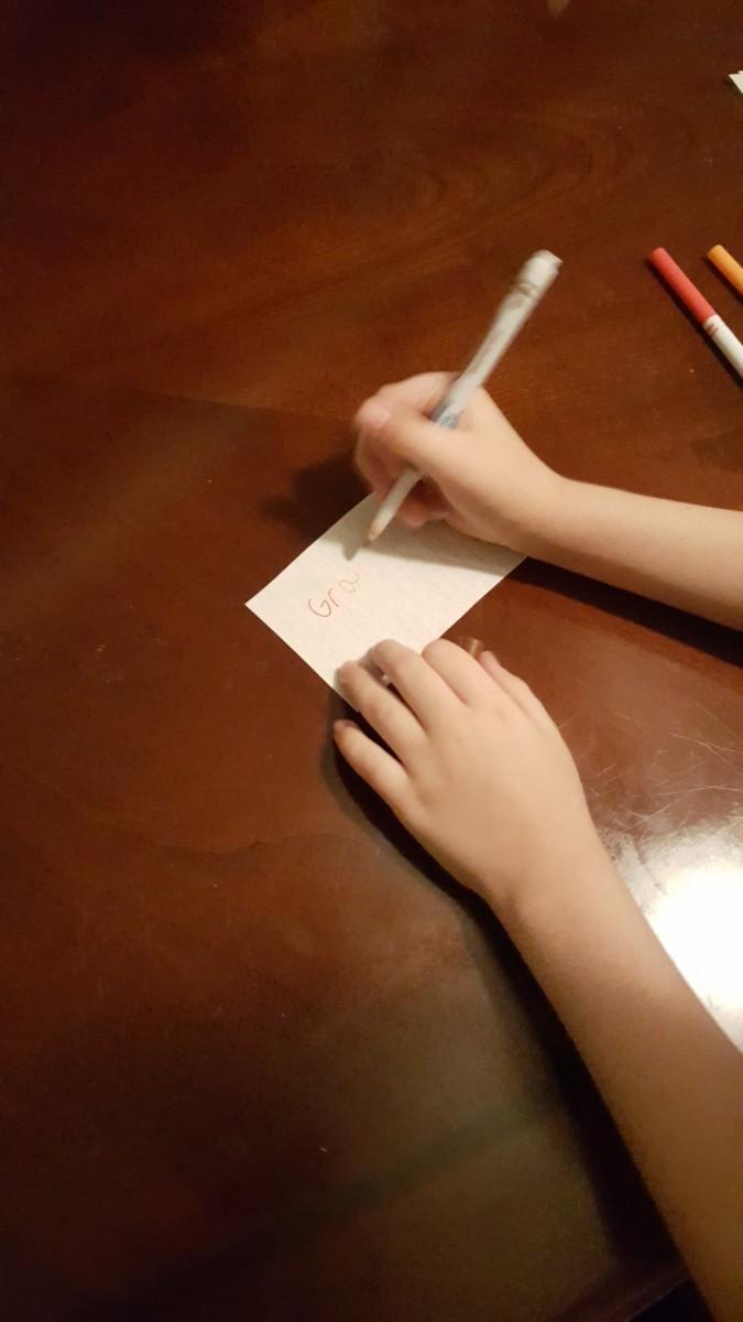 "Write ""Gratitude"" on a rectangular piece of paper."