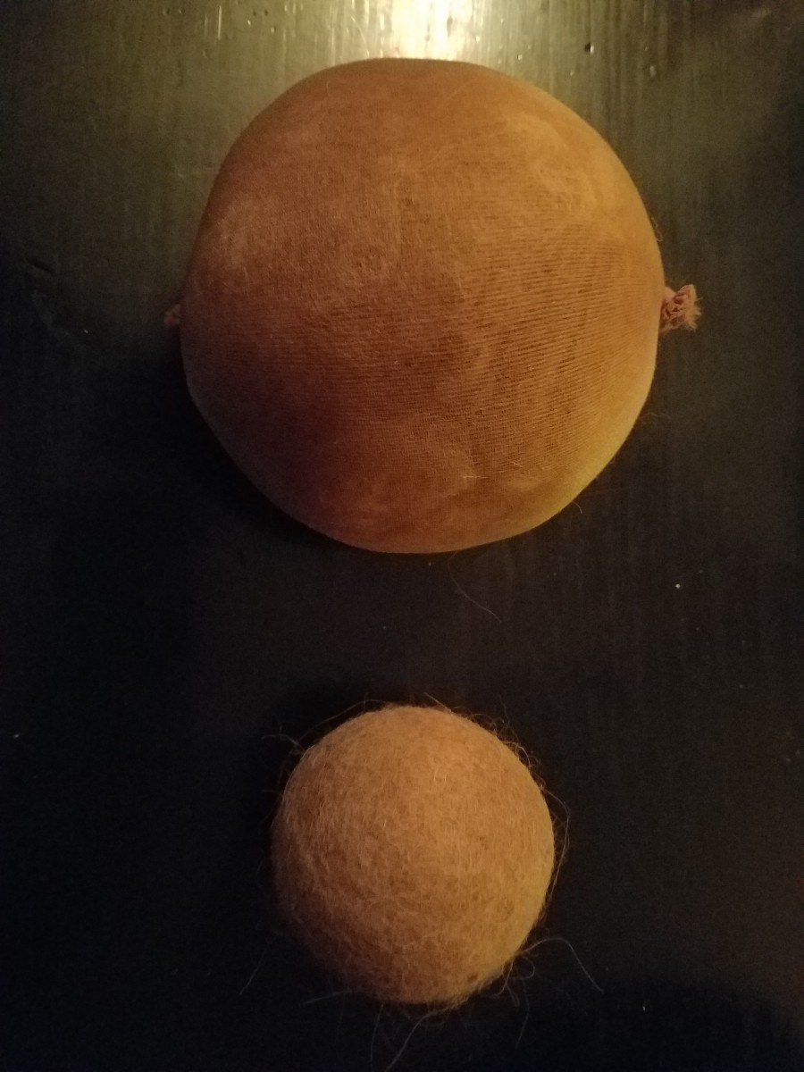 Dryer ball before and after washing, showing how much they shrink as they felt together.