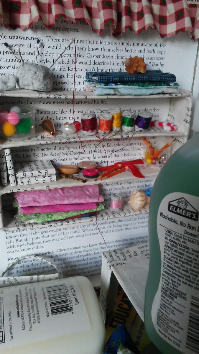Mini fabric bolts, mini thread spools, mini pom poms, and seashells decorate the shelves.