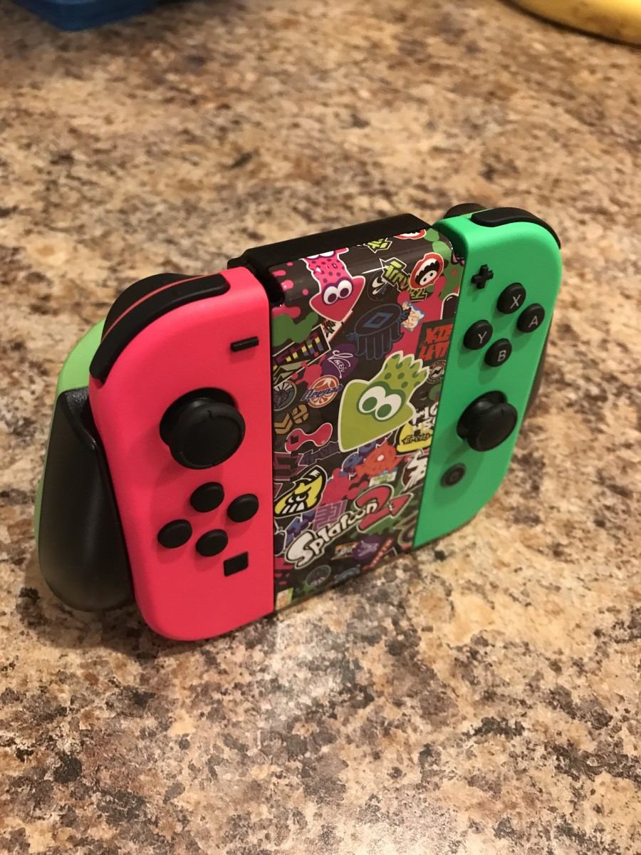 "The ""Splatoon 2"" PowerA Comfort Grip for Nintendo Switch with the ""Splatoon 2"" pink and green Joy-Cons."