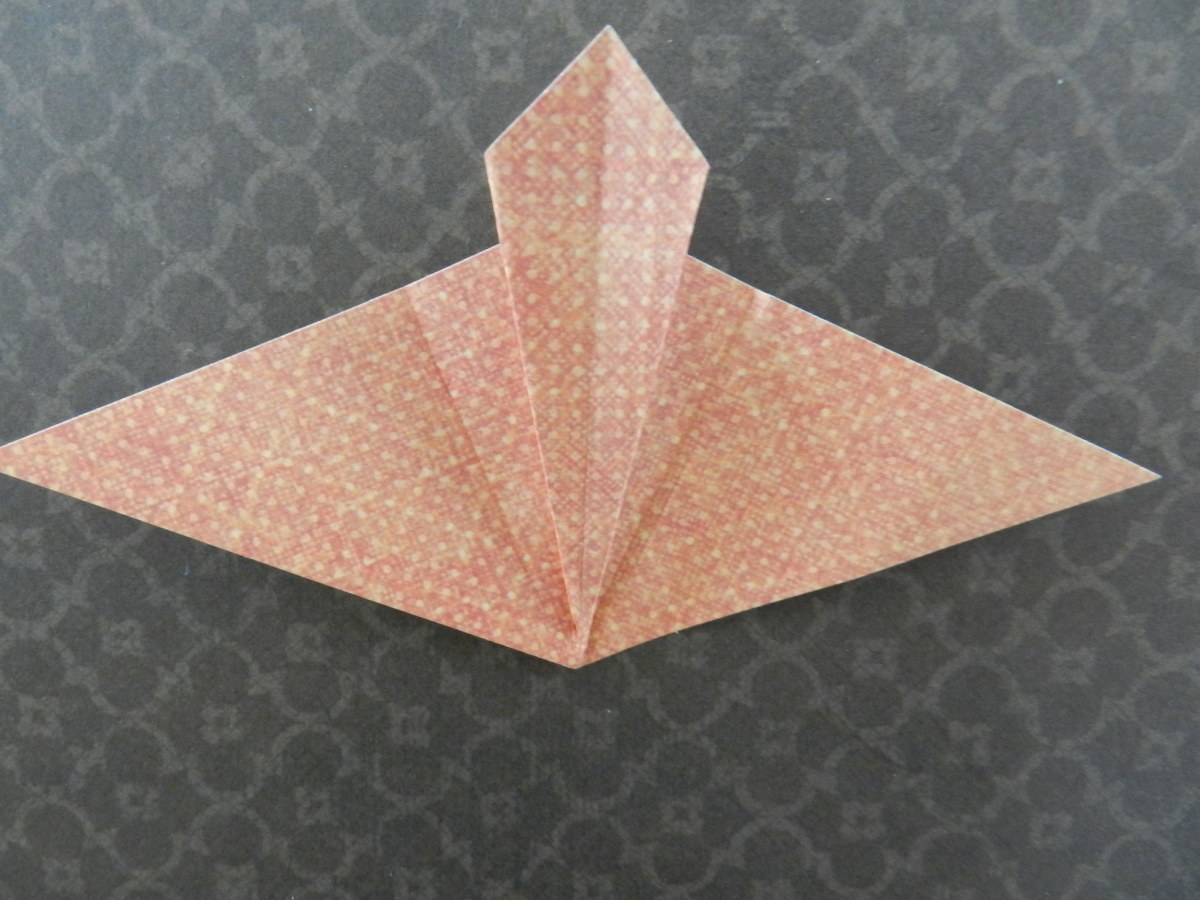 Open the triangle and refold creases to form a mountain as shown.
