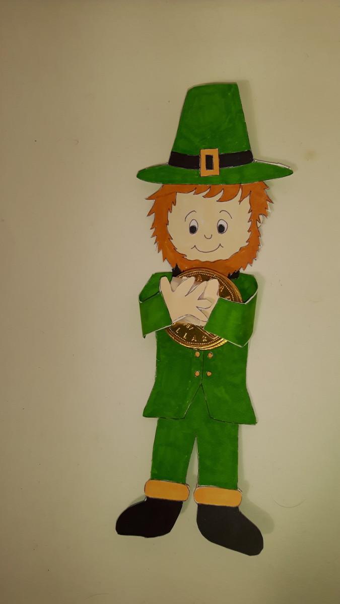 The leprechaun is holding his gold treasure.