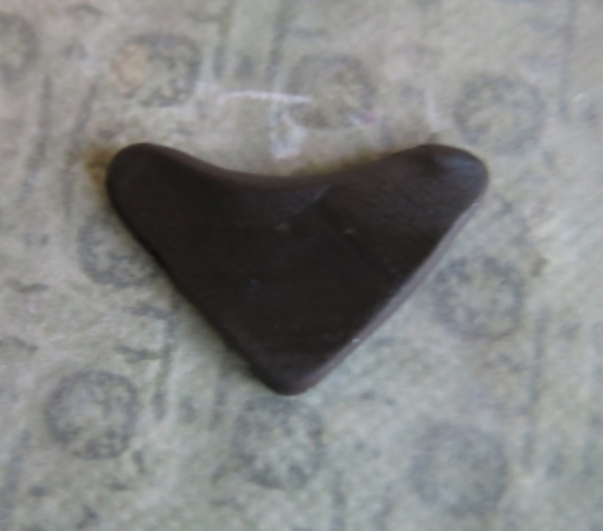Make the bird's mask by shaping the clay into a rounded triangle, like this.