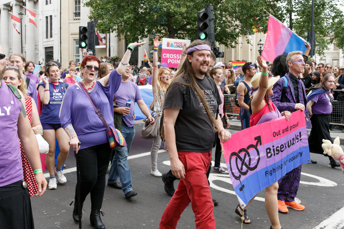 Bi people marching in a Pride parade in London.