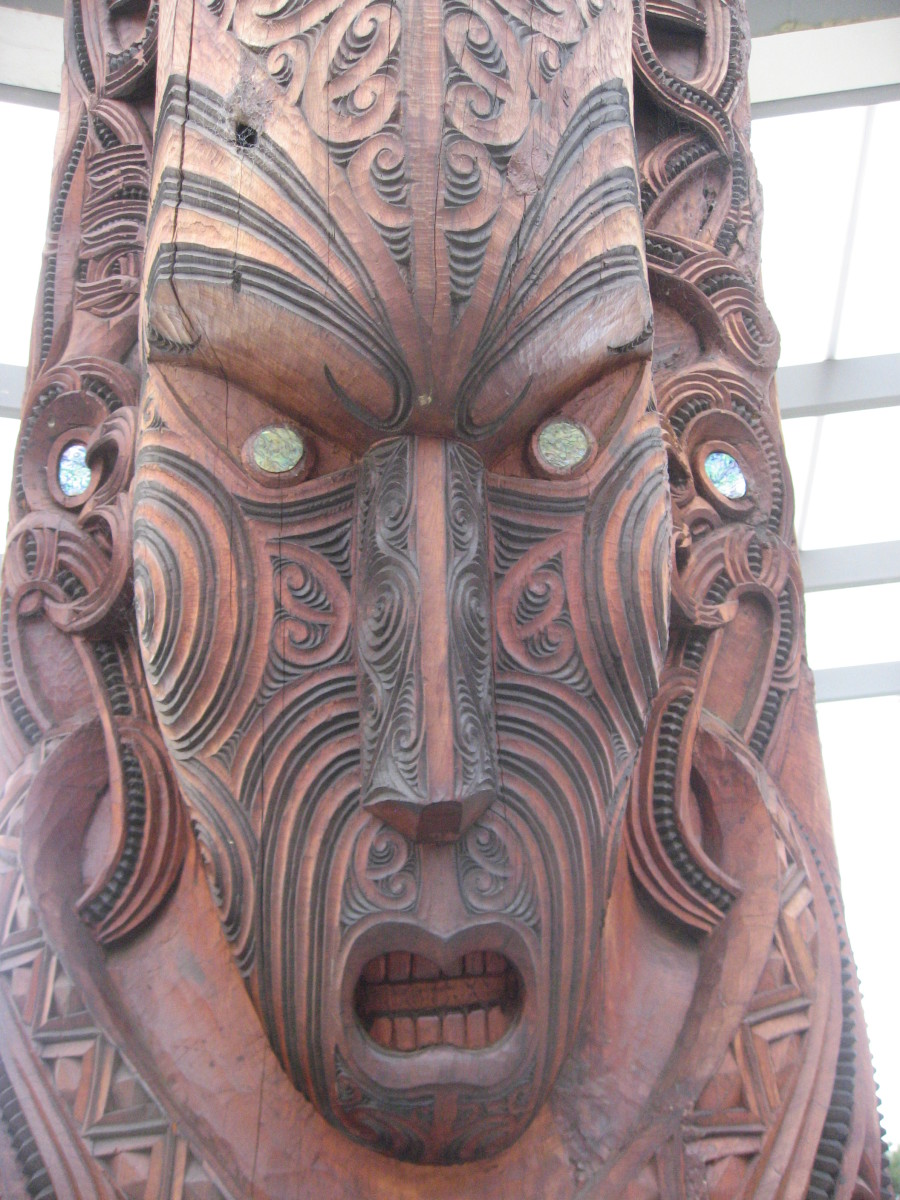 Face detail from Maori totem pole at Rotorua Maori Cultural Ceter. Note the simple  facial features with elaborate facial lines to mimic the Maroir identifying tattoos.