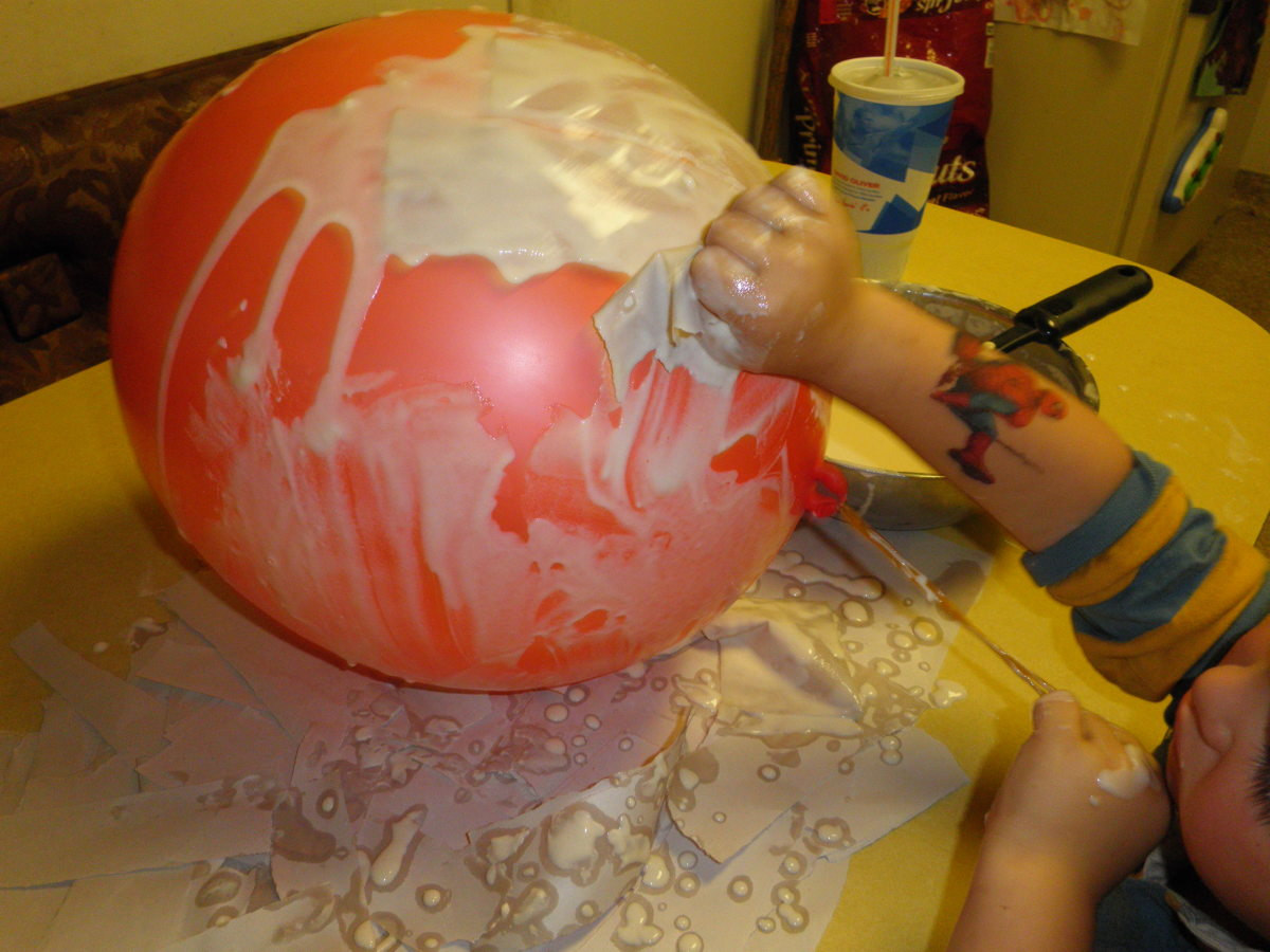 Dip the paper in the paper mache glue and apply in layers to the balloon.