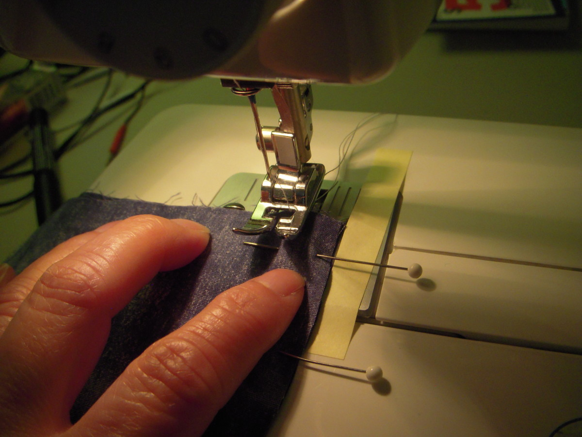 "Place the garment that you're sewing under the sewing foot, lining up the sewing edge to your 5/8"" mark. The sewing needle is close to the top edge, or the start of your seam."