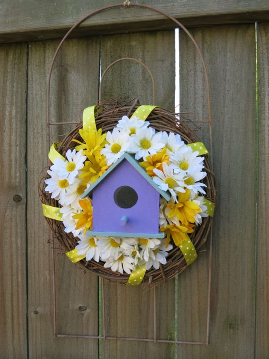 a charming welcome wreath using a garden fence piece, bird house, and some artificial flowers