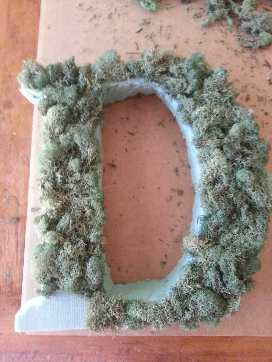 Continuing to cover the Styrofoam letter with moss