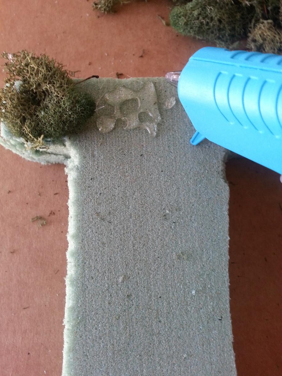 Gluing moss to Styrofoam letter.