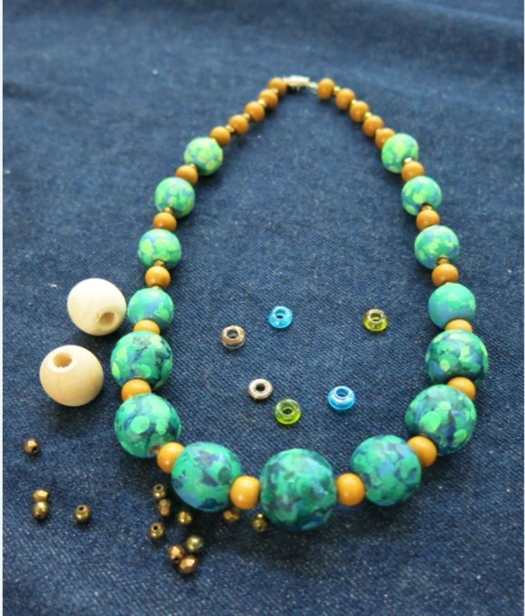 Adding extra beads to make a unique hand painted necklace
