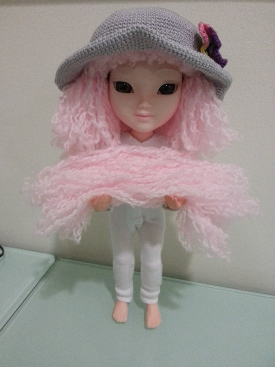 My Makies doll carrying the yarn taken out of the wig.