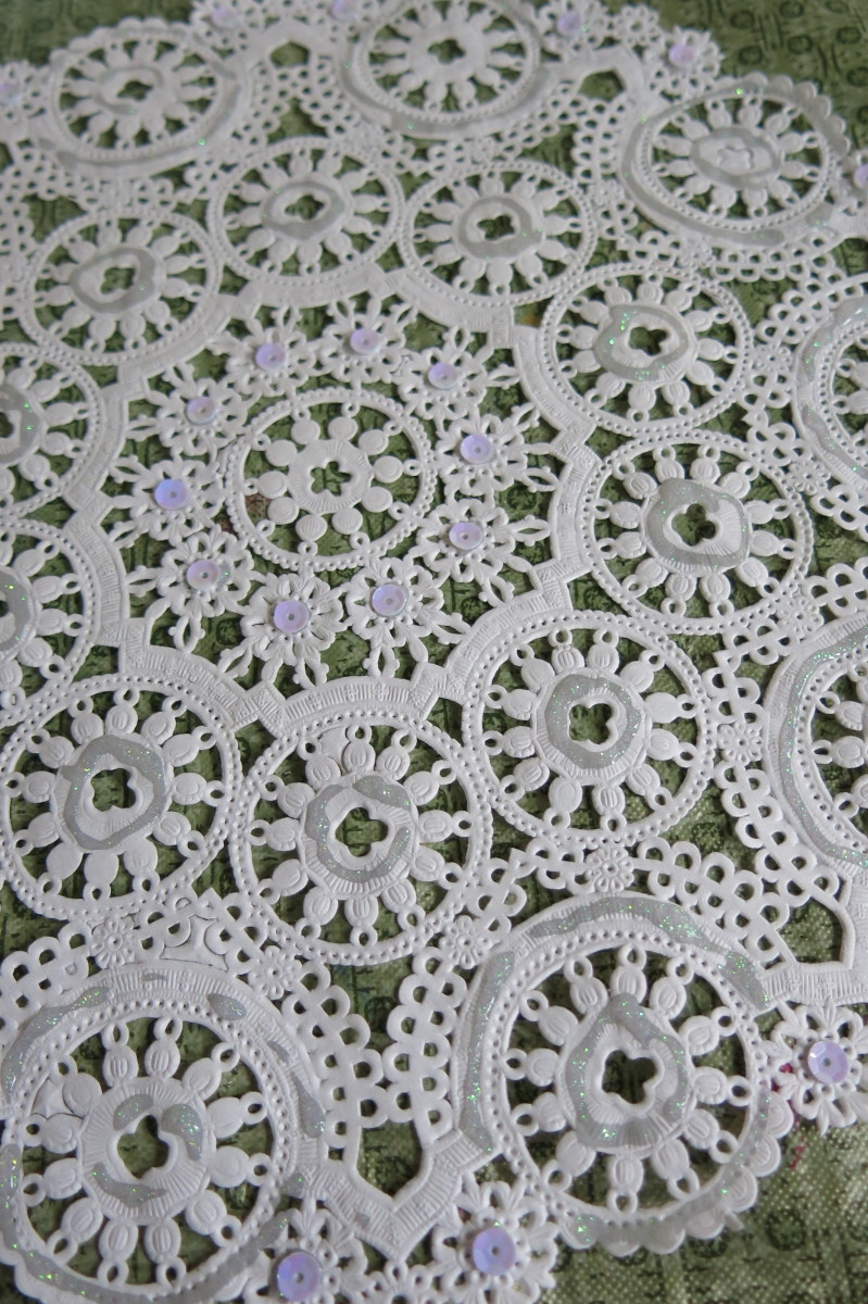 Decorate you paper doily with glitter and sequin to add some sparkle to your paper angel.