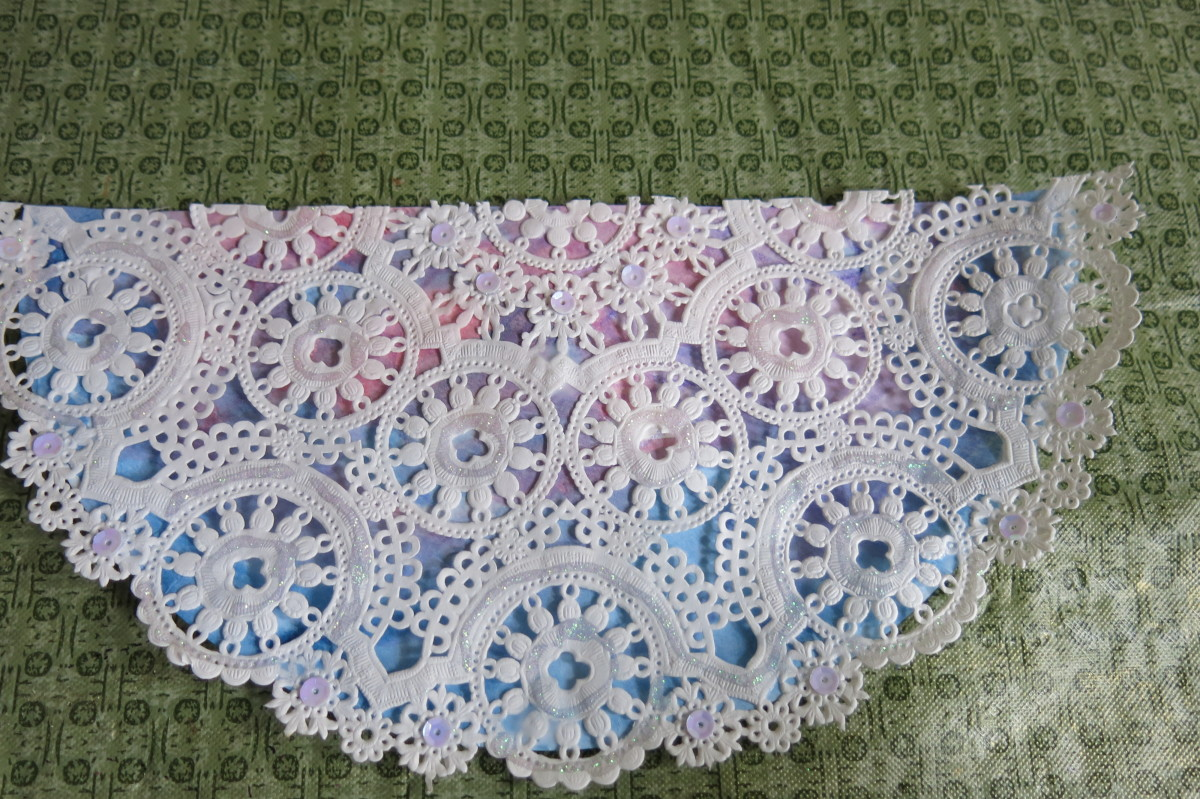Gluing your doily on the bottom half of your paper plate angel