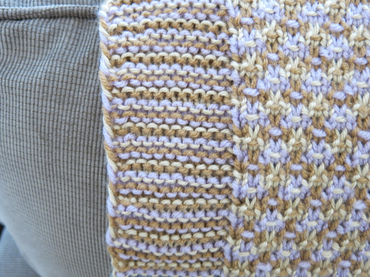 Close-up of yarn colors twisting up the side of the blanket edge.