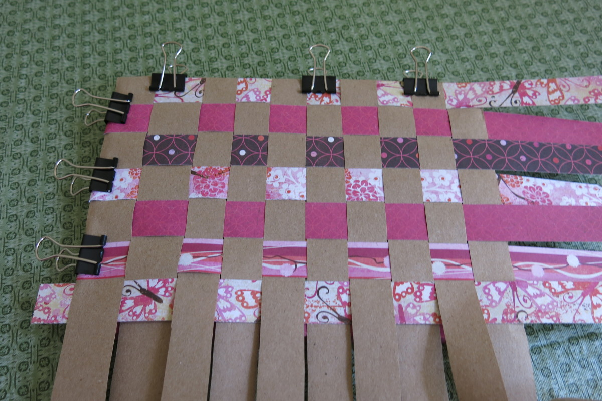 Begin to clip your woven paper design to the front cover of your book.