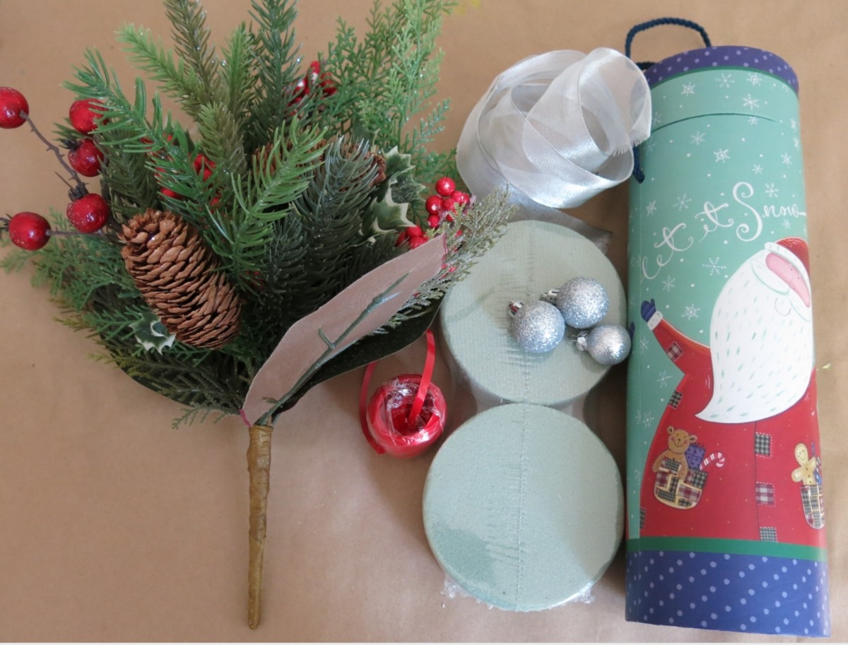 Materials for making a floral arrangement from a holiday gift box.