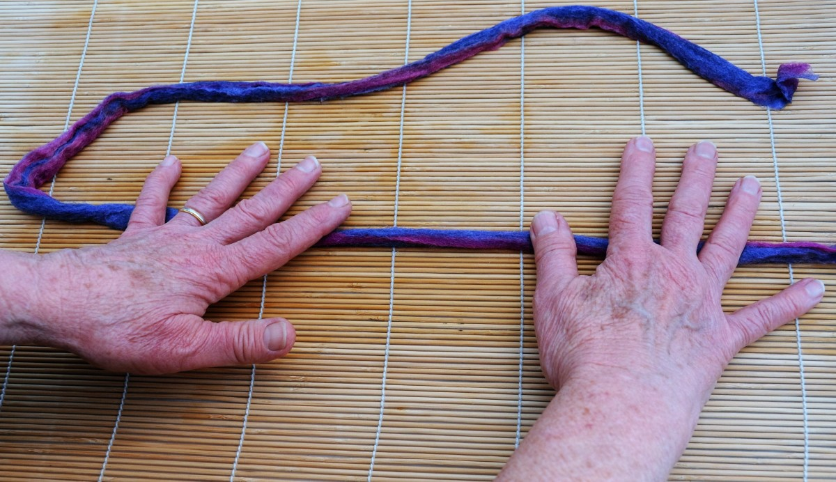 Begin rolling the dread into a cylindrical shape.  Press lightly at first.