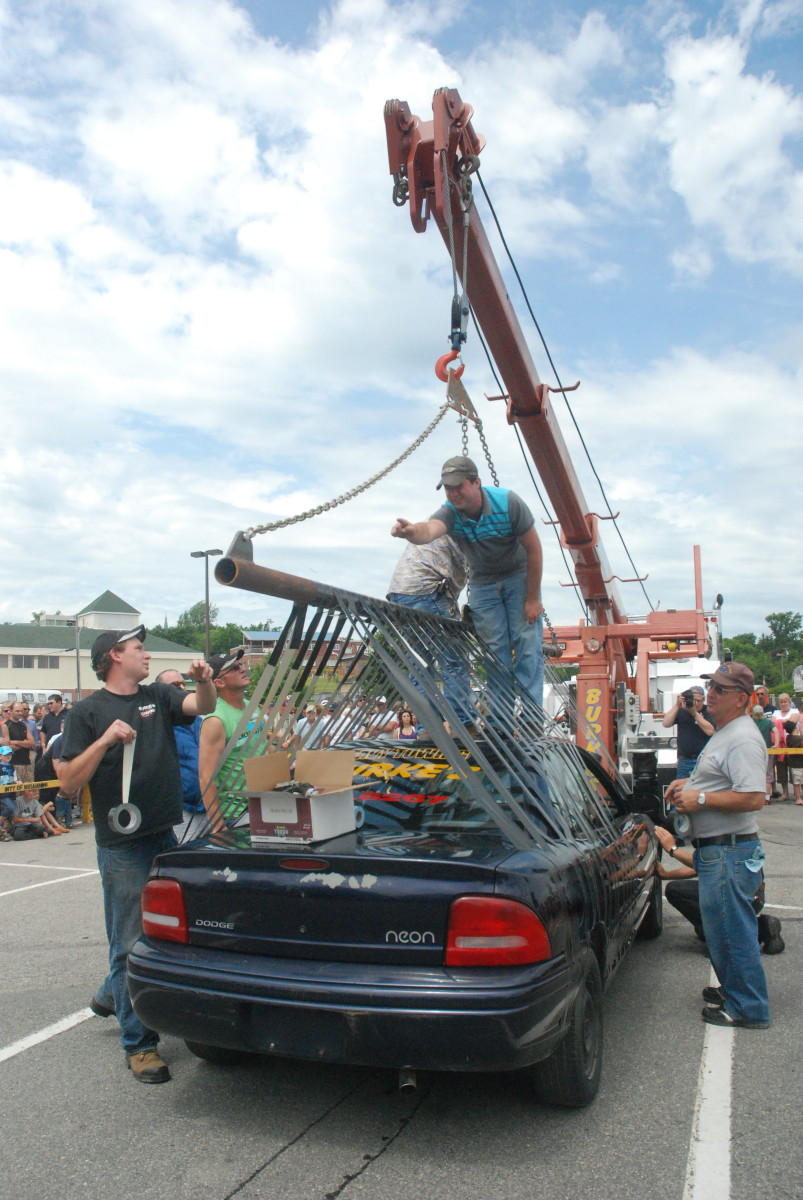 Volunteers use duct tape as they prepare to suspend a car in the air during a festival in Miramichi, New Brunswick.