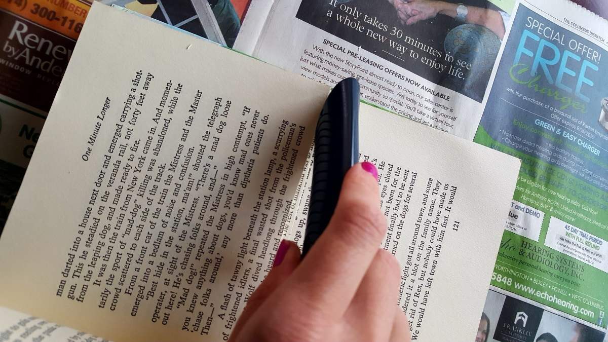 Using your utility knife, cut the pages in half.