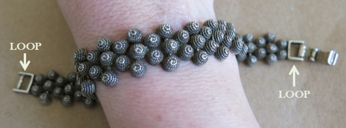 Choose a bracelet made of bendable links that has loops or rings at the ends.