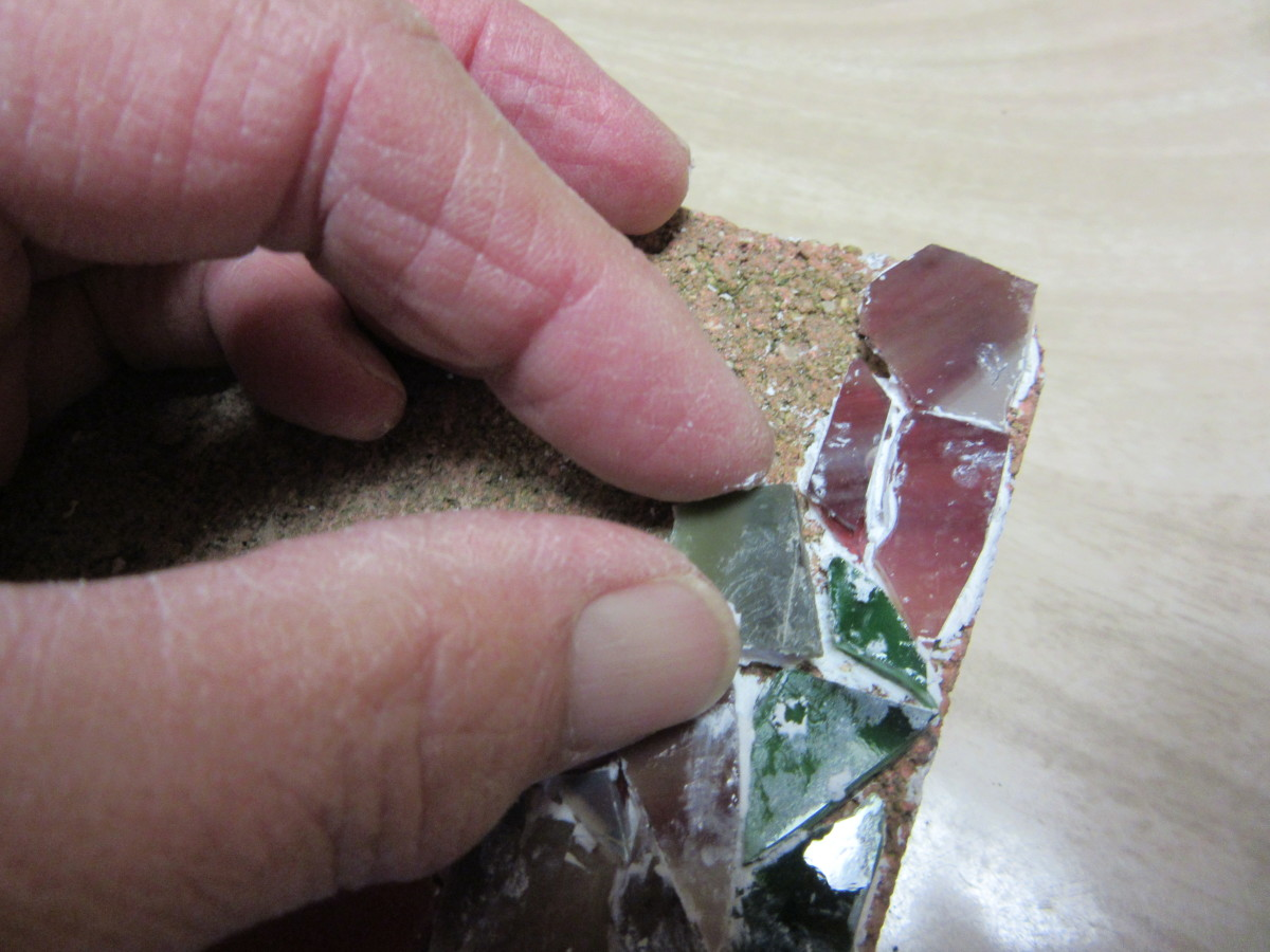 Firmly press the piece with the thin layer of adhesive into the design location