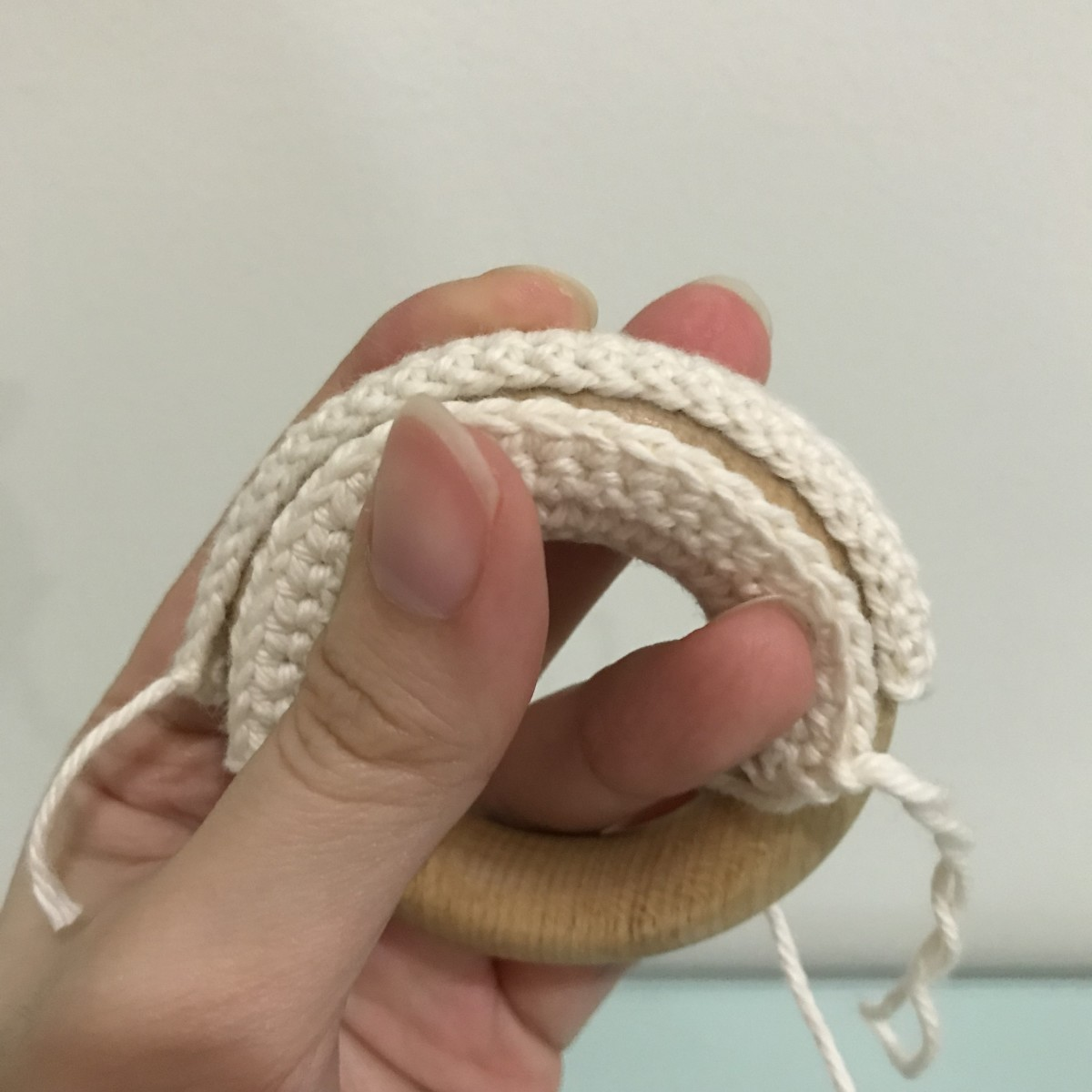 Once the rectangular piece can completely cover the wooden ring, fasten off and sew the piece closed with the tail end.
