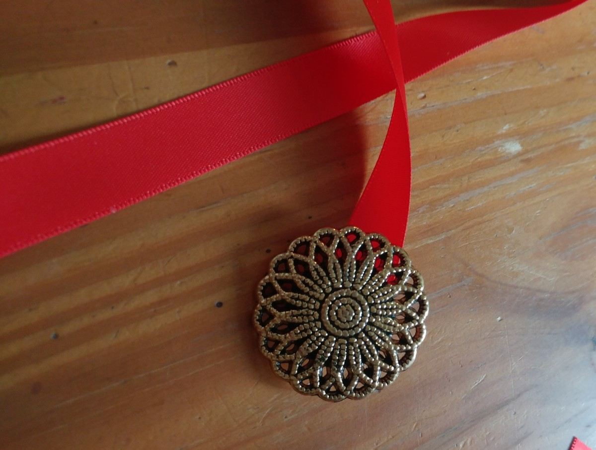 Sew a button on the other end of ribbon. A good sized button for the hair tie to fit over.