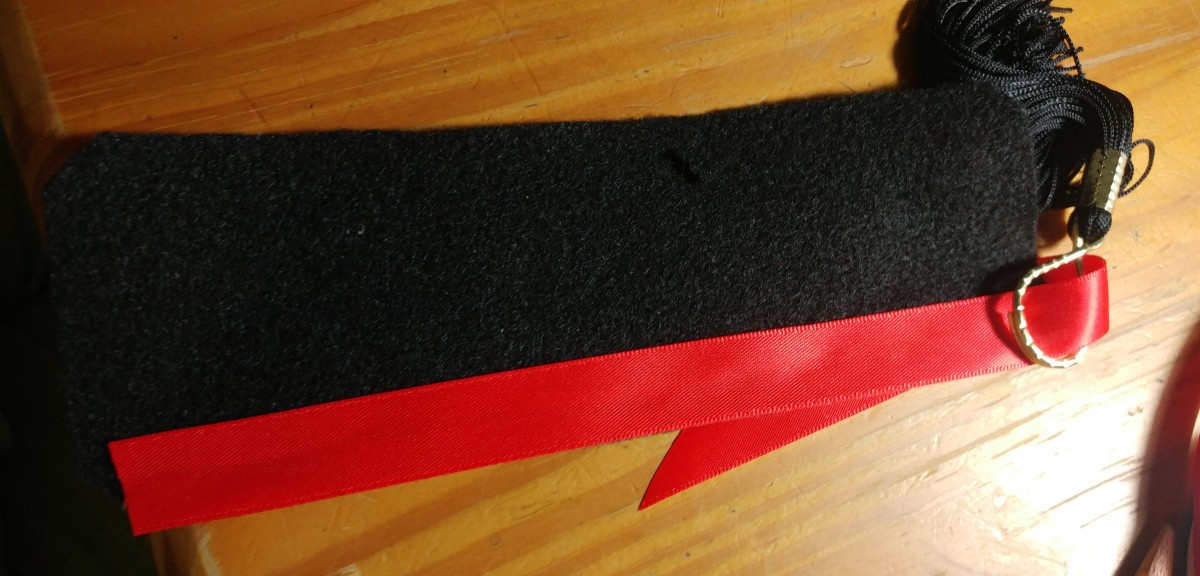 Glue the red ribbon behind the edge of the black felt. Then slip the tassel in.