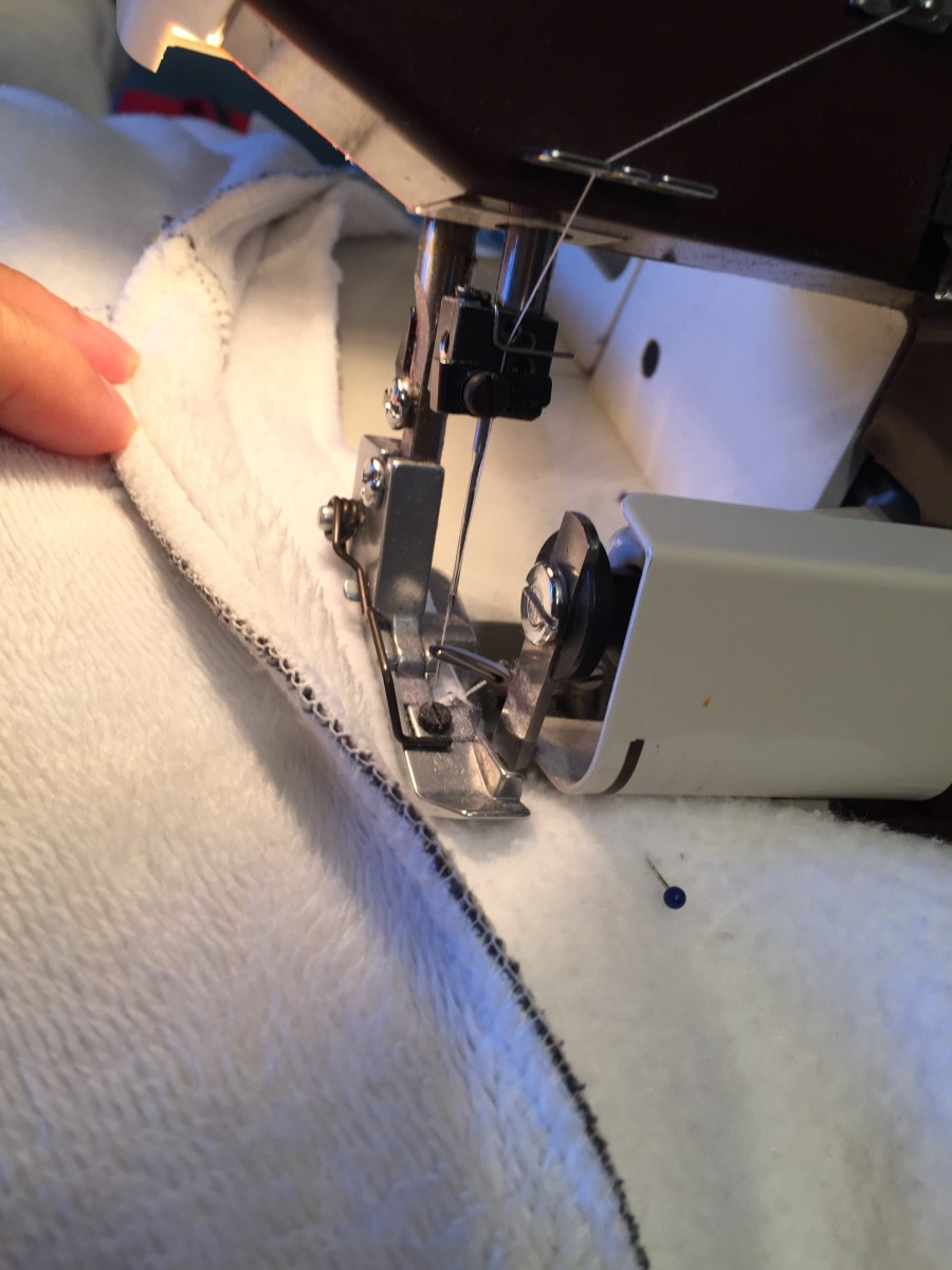 Here I am following the edge of the guide shirt. The serger blade will cut away the excess while also nicely finishing the edge. Be aware of your pins! The blade does not forgive!