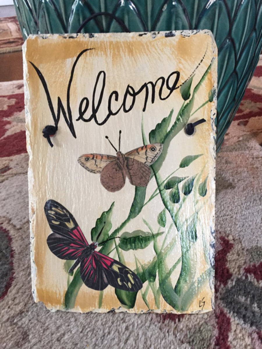 You can use a mix of paint and decoupage cutouts to create a fabulous welcome slate for your home (butterflies are hard to paint, but easy to decoupage!)