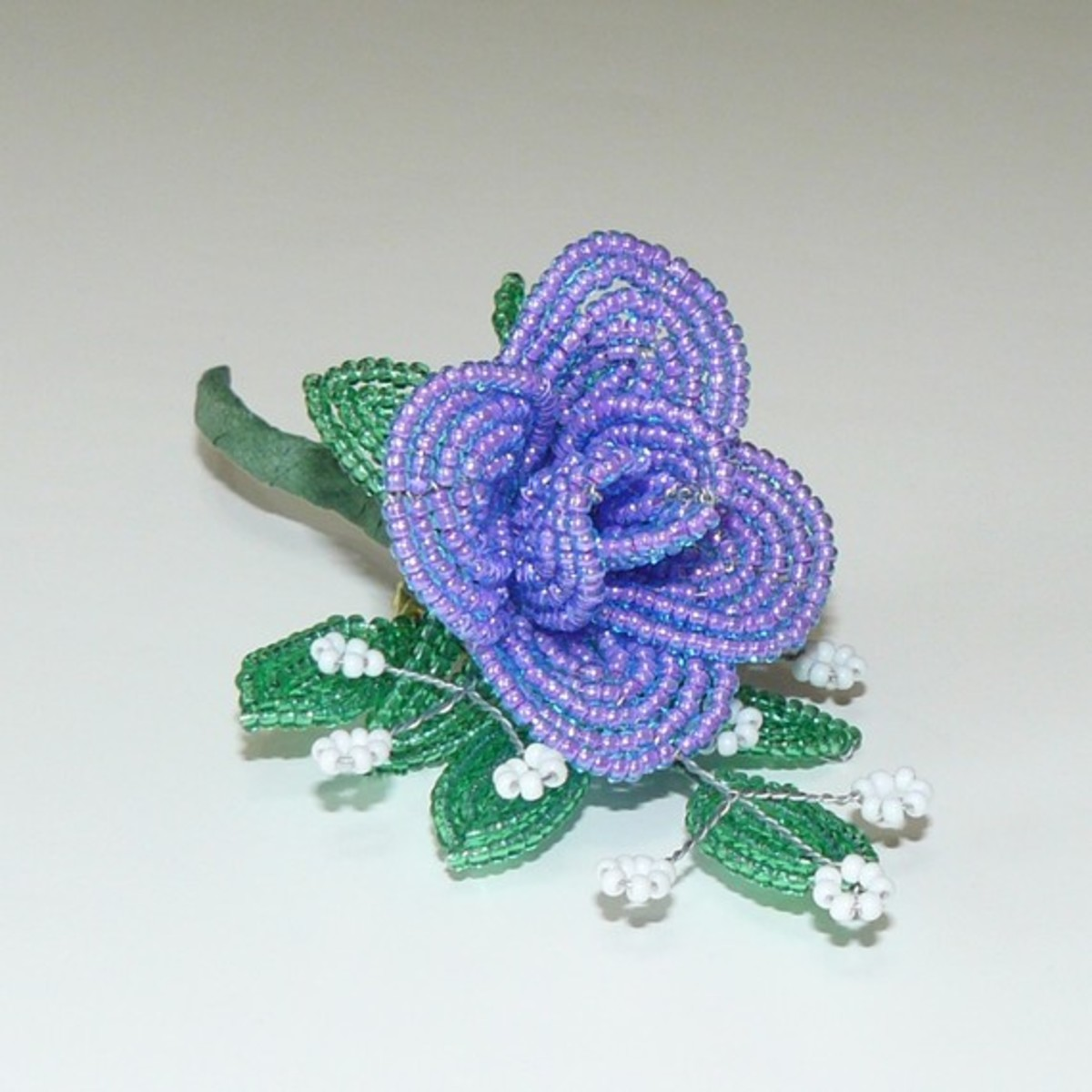 This flower brooch has a clip attached to the back of the spine.