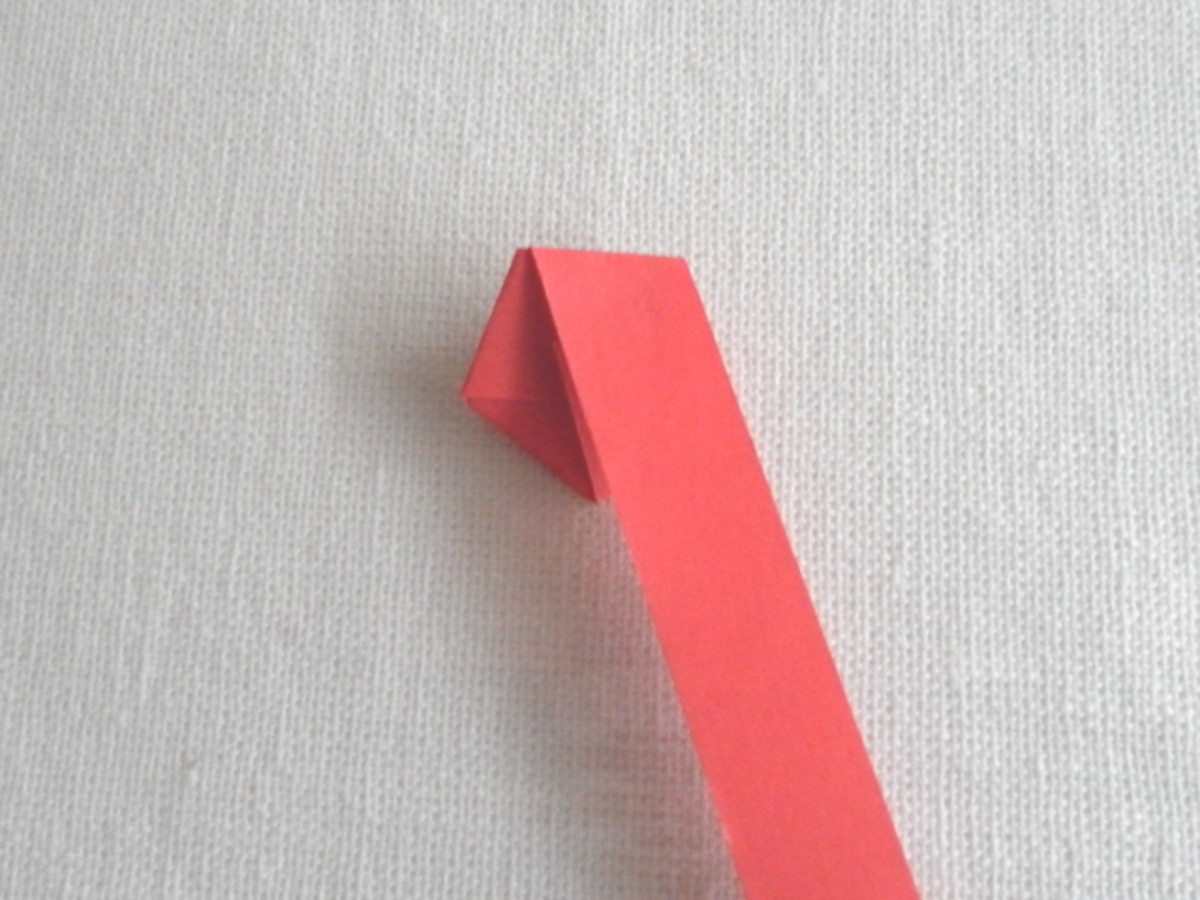 Wrap the long strip around the pentagon by aligning the edge and folding to the other side.