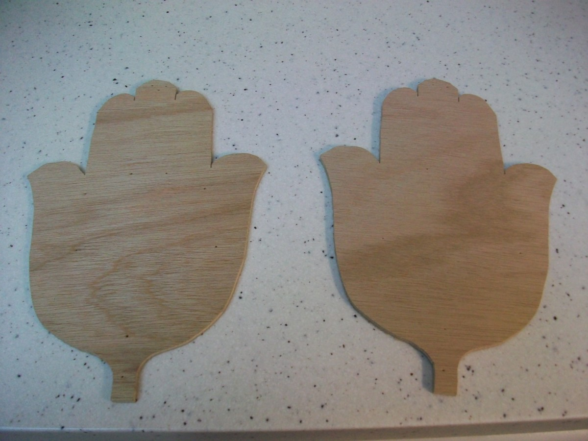 Two hamsas cut from Lauan plywood with a band saw.