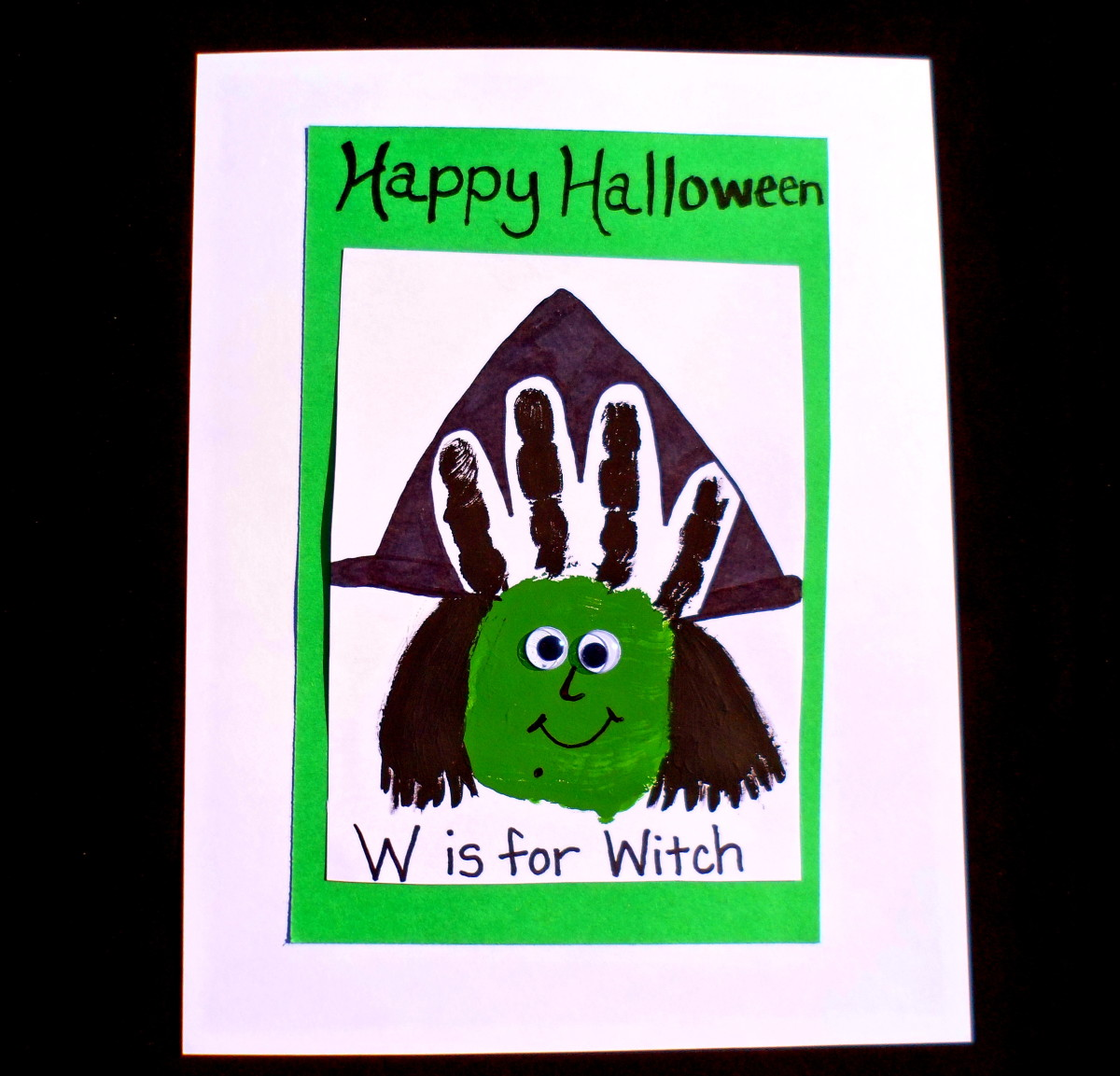 A handprint with green and black paint creates a cute witch.