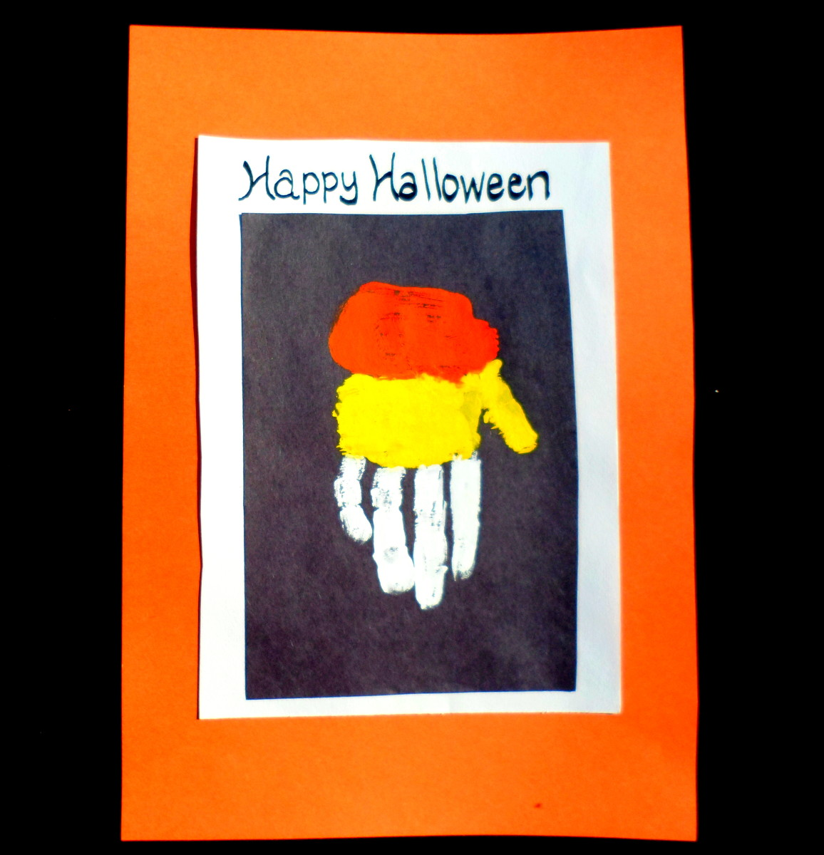 Apply orange, yellow, and white paint to your kid's hand to create a candy corn picture.
