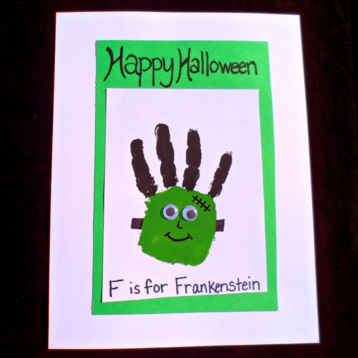 Apply green and black paint to your kid's hand to make a spooky frankenstein.