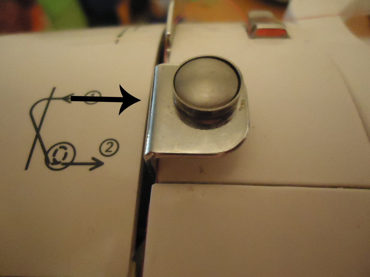 Thread is supposed to run behind  this metal part.  Apparently, this part is only for winding the bobbin.