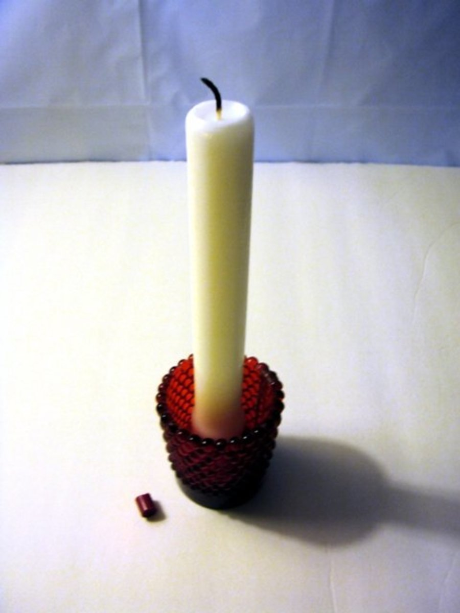 Burned down candle shown alongside cut red crayon piece