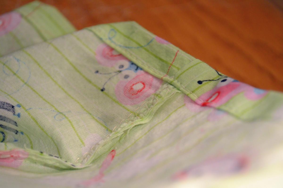 Sew sleeve into the hem of crib sheet.