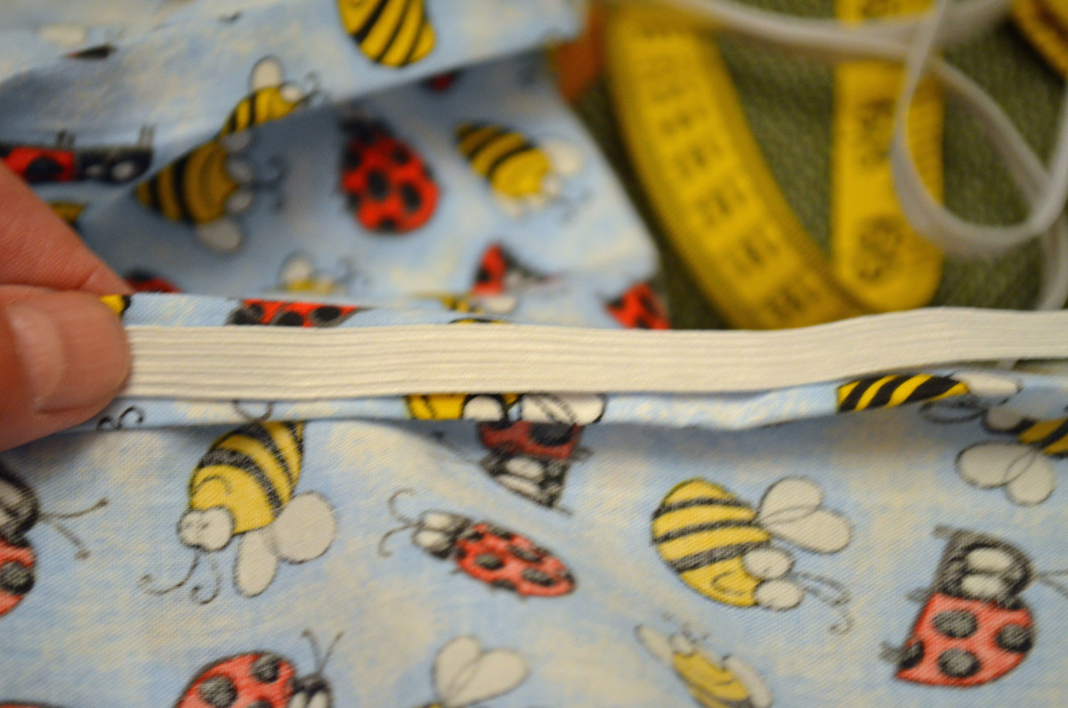 Lay the elastic on top of the turned down hem, then sew around stretching elastic as you go.