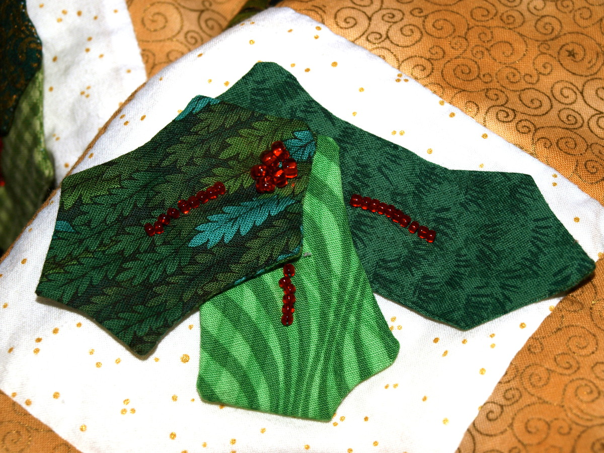 Fabric and beads combine to make a nice dimensional holly leaf embellishment on a Christmas quilt.