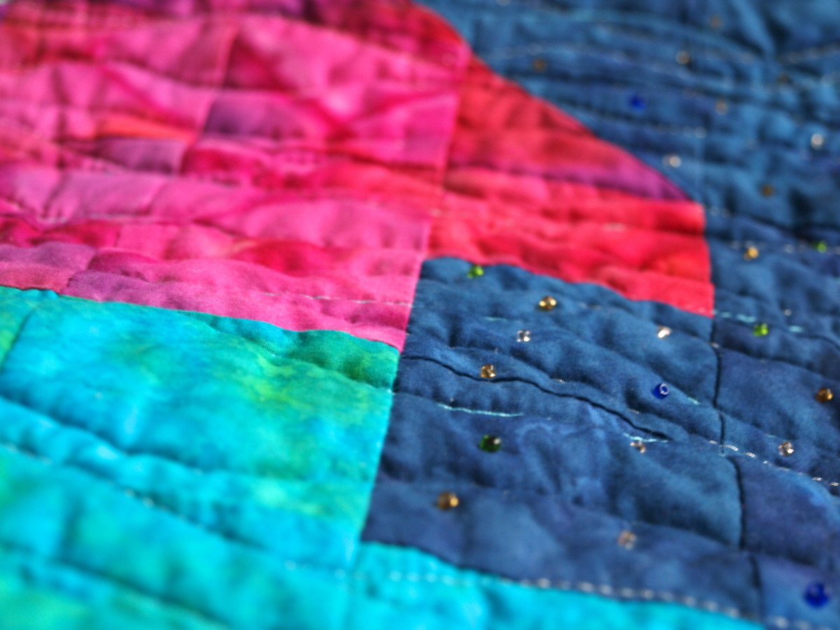 Small seed beads add just the right touch when looking for minimal embellishments.  Along with the flowing quilting, these beads were used to add sparkle and movement to the quilt.