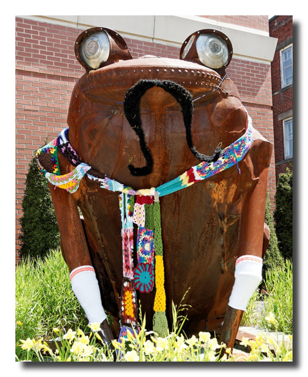Yarn bombed frog sculpture made from recycled materials.