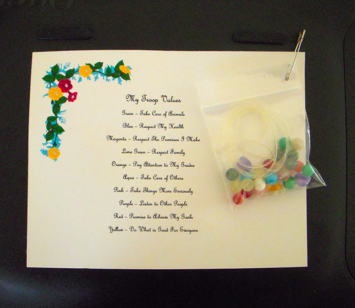 Troop values are represented by different colored beads. A pre-printed card that explains the meaning and value of each bead color is a part of this SWAP. Pin a small zip bag containing stretchy jewelry cording and beads.