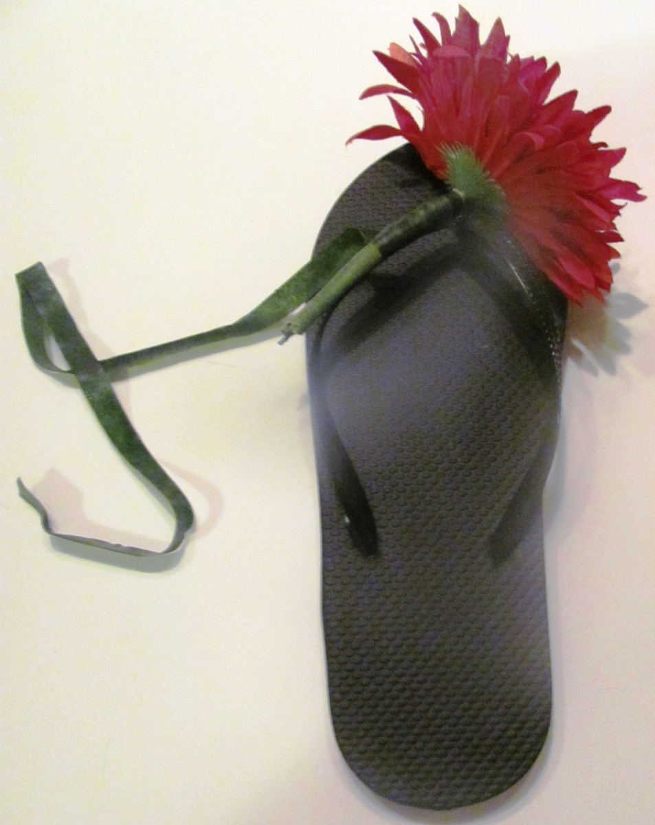 Use floral tape to securely fasten the flower stem to the top outside of the flip flop.