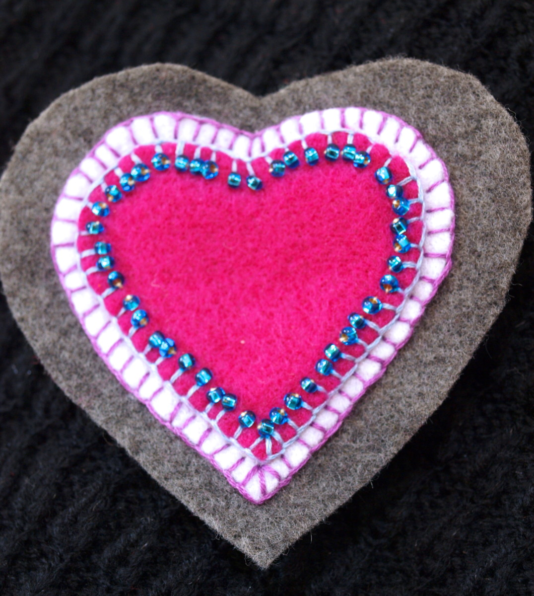 Here's another brooch using the same steps—a heart-shaped felt brooch. I used a blanket stitch for all the layers and added the blue beads after I had stitched the pink heart to the white heart.